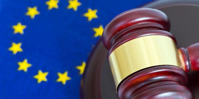 Europæisk lovgivning. Motiv med EU-flag og retshammer
