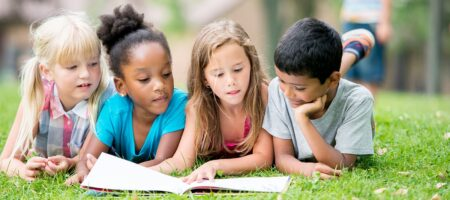 Reading children laying on grass field