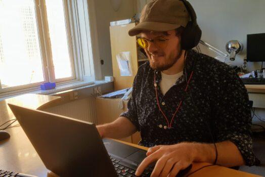 Gustav Kallan foran sin computer og med hovedtelefoner på.