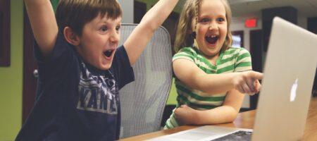 En dreng og en pige foran en computer. De jubler og er glade.
