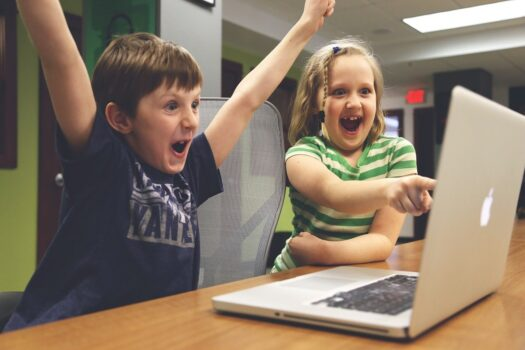 A happy boy and girl in front of a computer