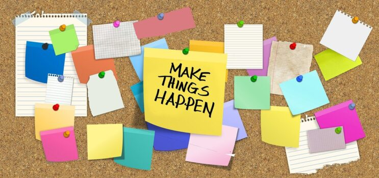 "Bulletin board with post-it saying ""Make things happen"""